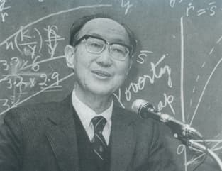 Portrait of S.C. Tsiang in front of a chalkboard full of equations.
