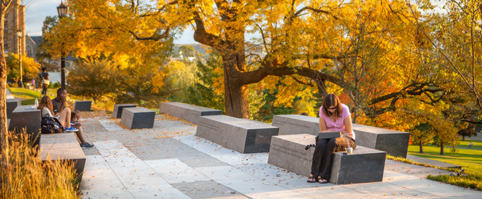 Student sitting on a bench on a fall day
