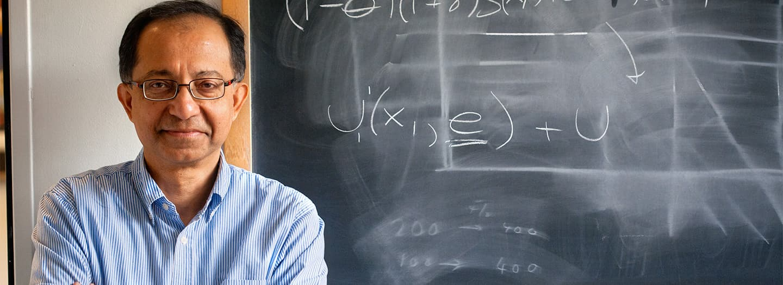 Kaushik Basu standing in front of chalkboard