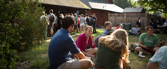 Students picnicing on the grass outside of the Big Red Barn.