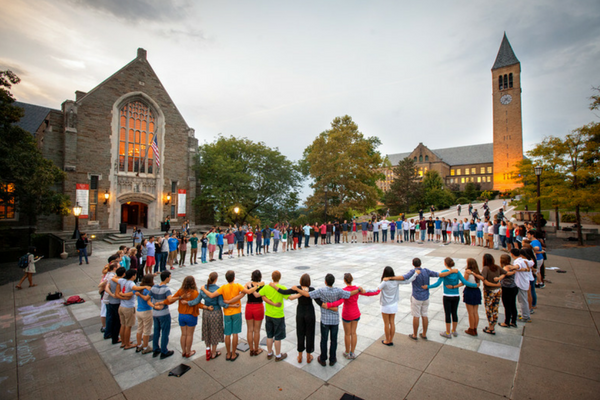 Students holding hands in a circle in front of Willard Straight Hall